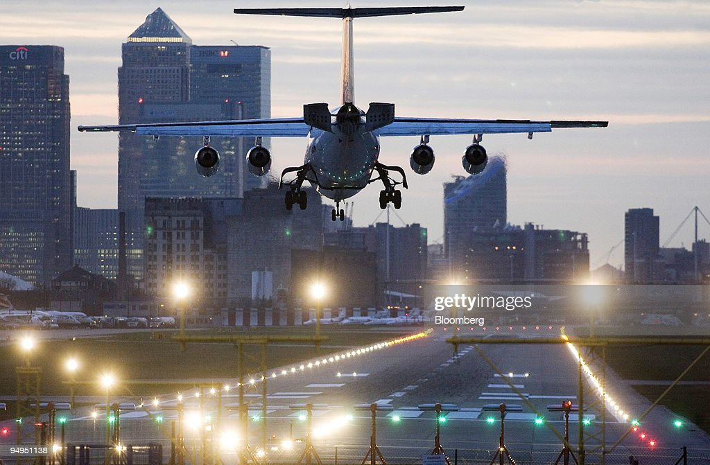 An airplane lands at London City airport with Canary Wharf i : News Photo