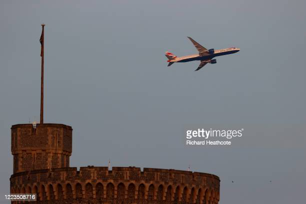 An airplane leaving Heathrow Airport flies over Windsor Castle on May 07, 2020 in Windsor, England. The country continued quarantine measures...