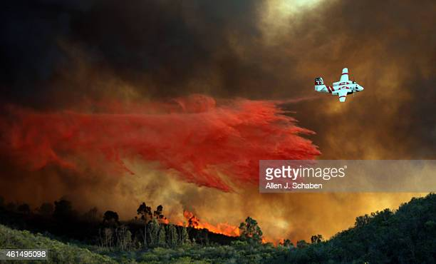 An airplane makes a fire retardant drop on a large hilltop home that had caught fire near Cal State San Marcos as crews battle a large wildfire...