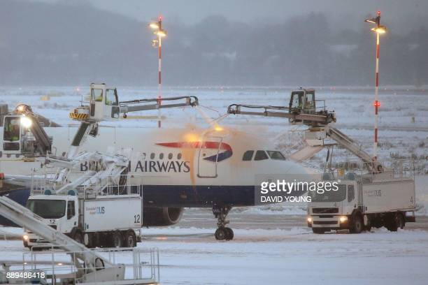 An airplane of British Airways is being deiced as it stands on the tarmac of the airport in Duesseldorf western Germany on December 10 2017 Due to...