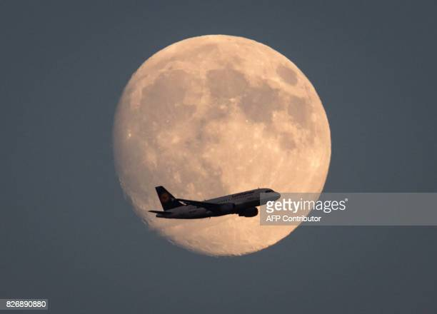 An airplane of German airline Lufthansa flies past the almost full moon as it prepares to land at the airport in Frankfurt am Main western Germany on...