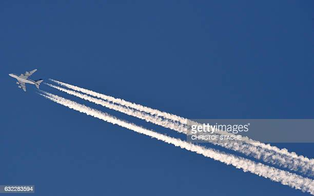 An airplane of Singapore Airlines draws a contrail in the blue sky over GarmischPartenkirchen southern Germany on January 21 2017 / AFP / Christof...