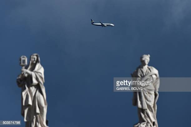 An airplane of the Irish lowcost airline Ryanair is seen in the sky above statues of the Vatican on January 6 2016 AFP PHOTO / GABRIEL BOUYS / AFP /...