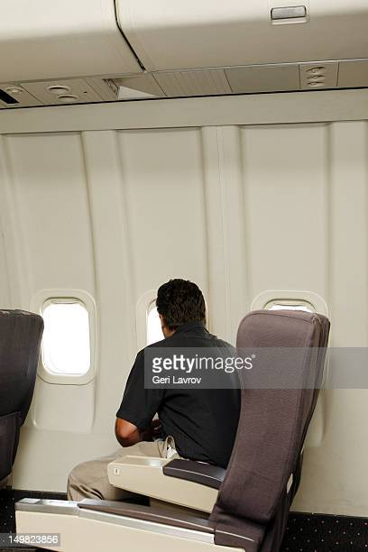 An airplane passenger looking out the window