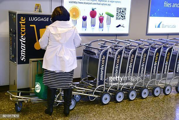An airplane passenger rents a luggage cart at a Smarte Carte vending station at Salt Lake City International Airport in Salt Lake City Utah Smarte...