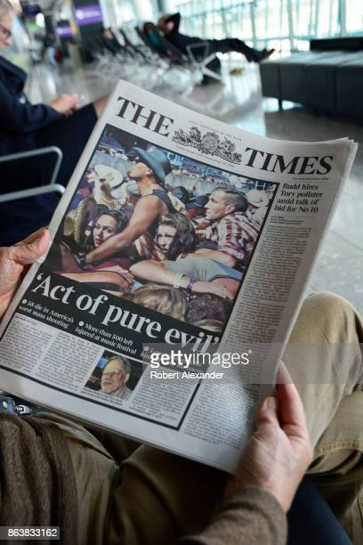 An airplane passenger waiting to board a flight at Heathrow International Airport in London, England, reads a copy of the London tabloid newspaper,...