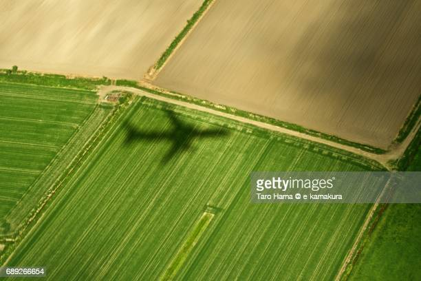 An airplane silhouette on fields in Chitose city in Hokkaido daytime aerial view from airplane