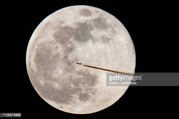 An airplane silhouettes against the Super Moon on February 19 2019 in Nuremberg southern Germany / Germany OUT