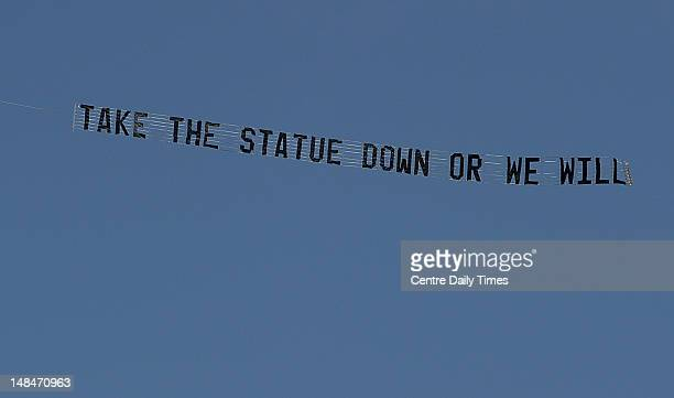 An airplane towing a banner that reads 'Take the statue down or we will' flies over the Penn State campus for several hours Tuesday July 17 in State...