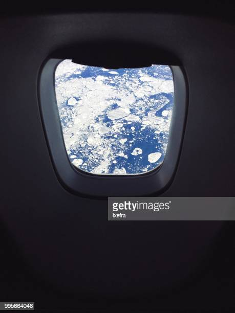 An airplane window revealing icy landscape outside