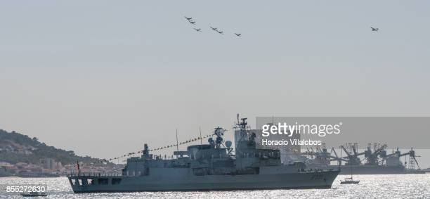 An airplanes formation flies above Portuguese Navy frigate NRP frigate Alvares Cabral laying at anchor in Tagus River during the commemoration of the...