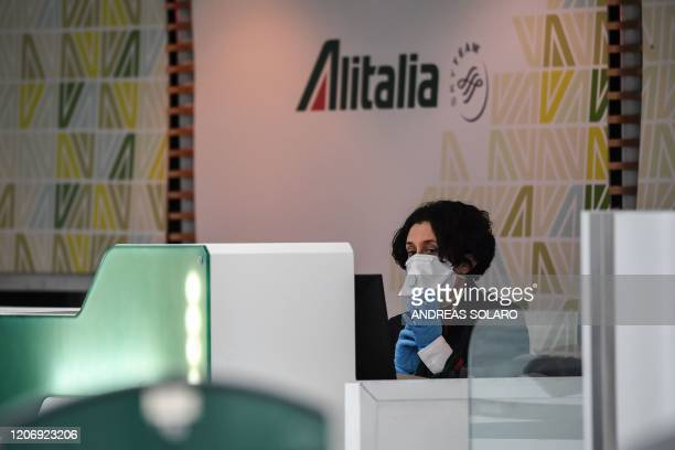 An airport Alitalia staff wearing a respiratory mask and gloves looks on at Rome's Fiumicino international airport March 13 2020 Rome's Ciampino...