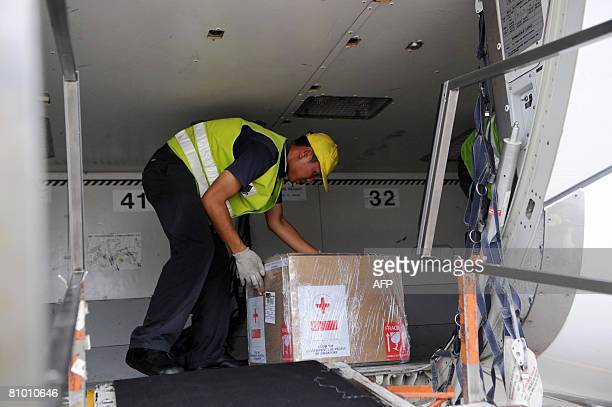 An airport baggage handler load box of medical supplies bound for Myanmar on a commercial flight at the Changi International airport in Singapore on...