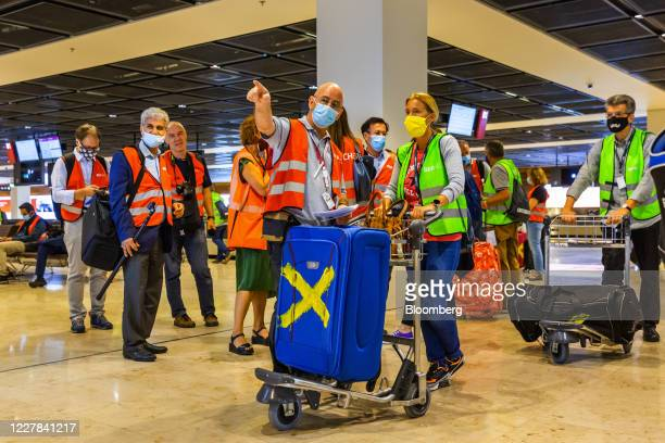 An airport employee, center left, wears a protective face mask as he directs a volunteer during a passenger check-in test run demonstration at Berlin...