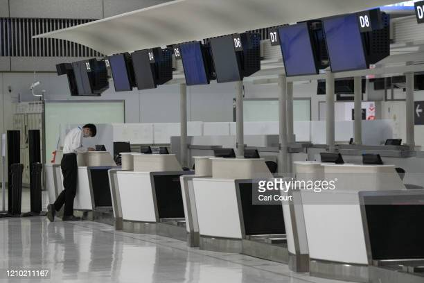 An airport employee checks his phone next to empty check-in desks at Narita Airport on April 17, 2020 in Tokyo, Japan. Narita Airport, one of Japans...