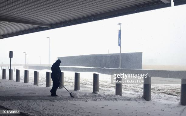 An airport employee shovels snow at the curb of the departures dropoff area at Terminal five John F Kennedy International Airport on January 4 2018...