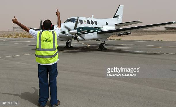 An airport employee signals to a twinpropeller Beechcraft plane that is fixed with salt flares which are fired into a promising cloud to increase...