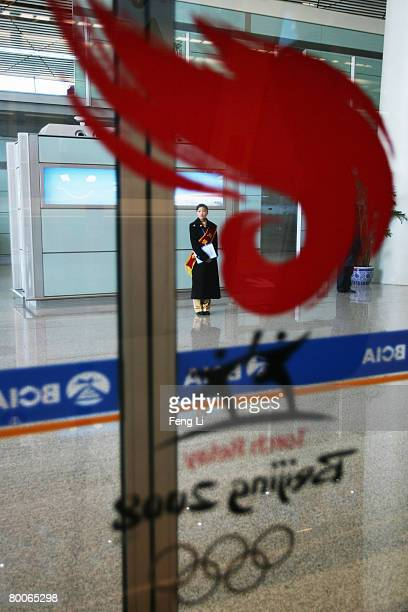An airport employee stands behind the logo of torch relay of Olympic Games at the new terminal building T3 at the Beijing Capital International...