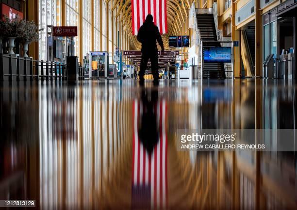 TOPSHOT An airport employee walks through Ronald Reagan Washington National Airport in Arlington Virginia on May 12 2020 The airline industry has...