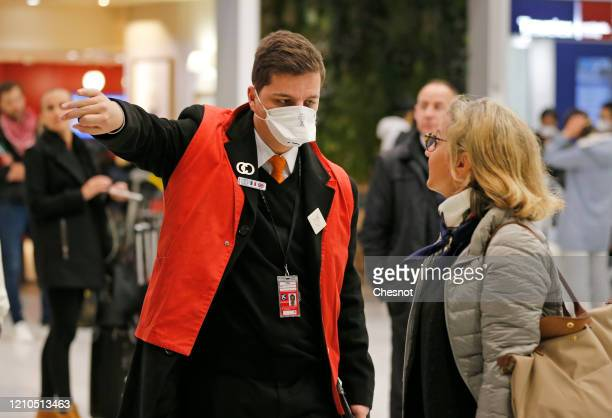 An Airport employee wearing a protective mask greets a passenger from China after landing at Roissy Charles de Gaulle airport on March 5, 2020 in...
