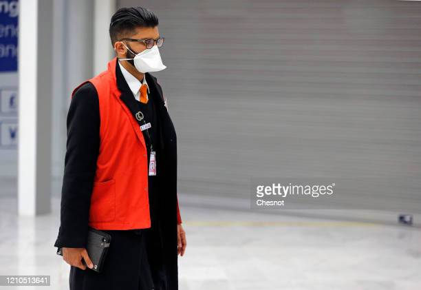 An Airport employee wearing a protective mask waits to greet passengers from China after landing at Roissy Charles de Gaulle airport on March 5, 2020...
