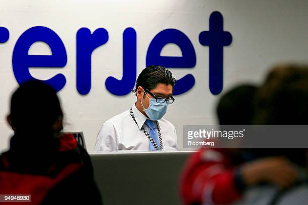 An airport employee wears a surgical mask while checking passengers in at Benito Juarez International Airport in Mexico City Mexico on Tuesday April...