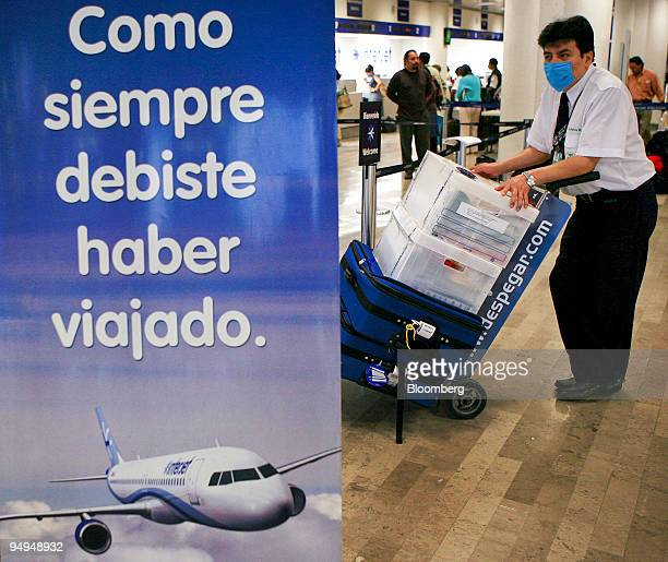An airport employee wears a surgical mask while transporting baggage at Benito Juarez International Airport in Mexico City Mexico on Tuesday April 28...