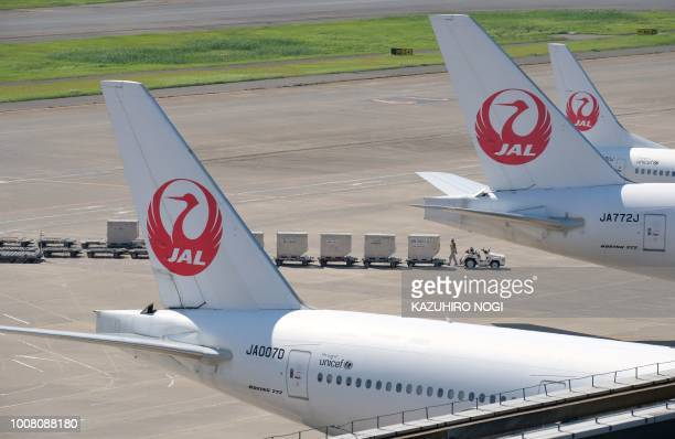 An airport employee works under passenger planes of Japan Airlines at Tokyo's Haneda airport on July 31 2018 Major Japanese carriers All Nippon...