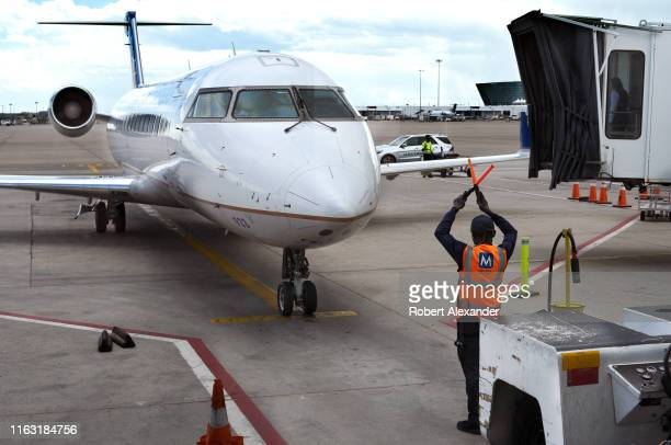 An airport ground crew member gives a hand signal to the pilot of a United Express plane preparing to depart Denver International Airport in Denver...