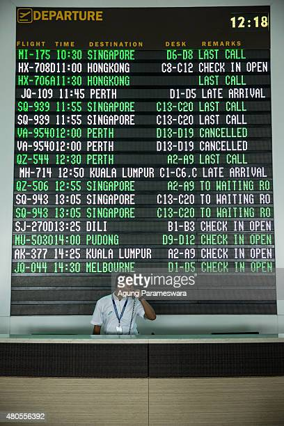 An airport officer is seen received a call infront of flight information board at Ngurah Rai international airport departure on July 13 2015 in...