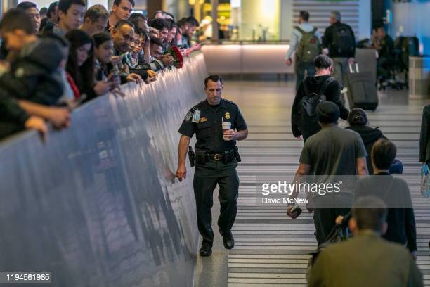 An airport officer walks past international travelers arriving to Los Angeles International Airport on the first day of health screenings for...