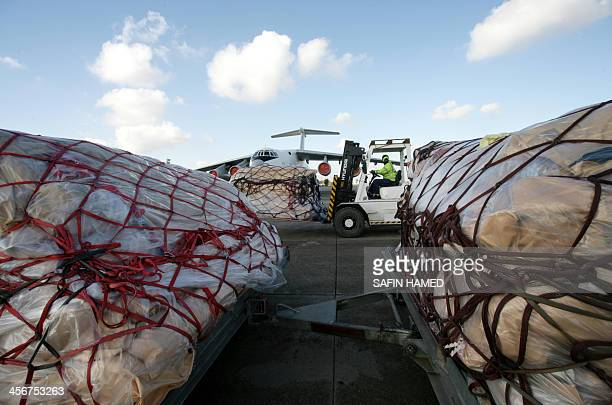An airport official drives a pick up truck carrying packages of aid onto a plane carrying roughly 40 metric tonnes of international aid from the...