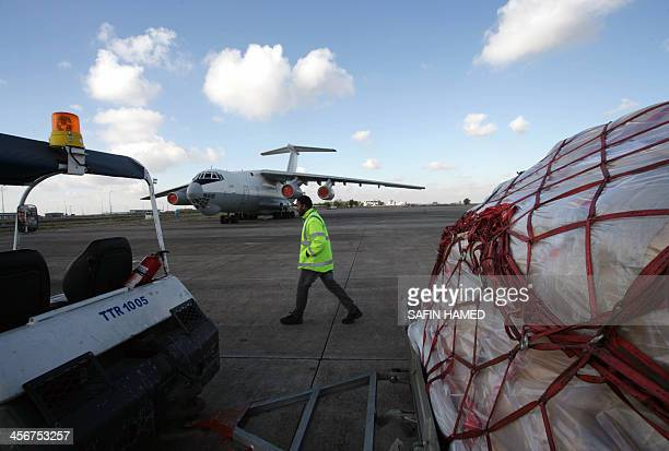 An airport official walks in front of a plane carrying international aid from the World Food Programme and the United National High Commissioner for...