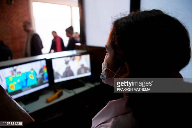 An airport oficial, wearing a face mask, checks the screen of a thermal scanner as passengers arrive at the Tribhuvan International Airport after...