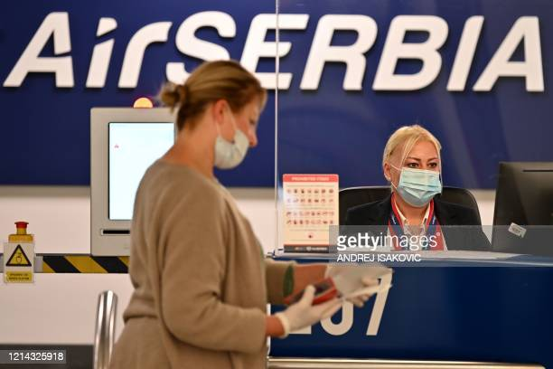 An airport personnel wearing a protective face mask, serves a passenger behind plexiglas at the check-in counter at Belgrade's airport on May 21 as...