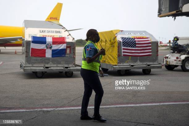 An airport security personnel stands guard as an eployee moves shipping containers with 228,150 doses of the Pfizer-BioNTech vaccine against...
