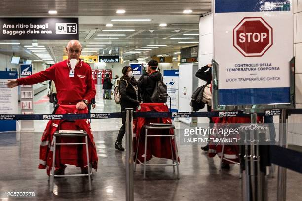 An airport staff directs passengers exiting an airplane that landed at Rome's Fiumicino airport from Paris on March 7 2020 as part of body...