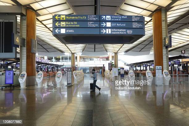 An airport staff wearing protective mask walks past an empty self check in kiosk at the departure terminal at Changi Airport on March 24, 2020 in...