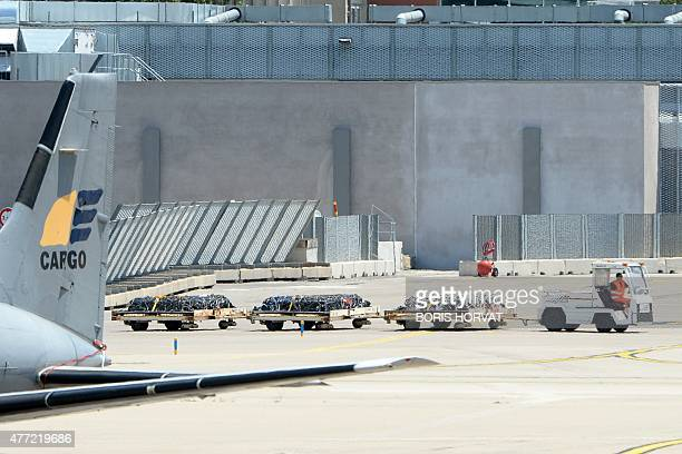 An airport vehicle pulls cargo platforms bearing coffins with the remains of Spanish victims of the Germanwings flight crash on the tarmac of the...