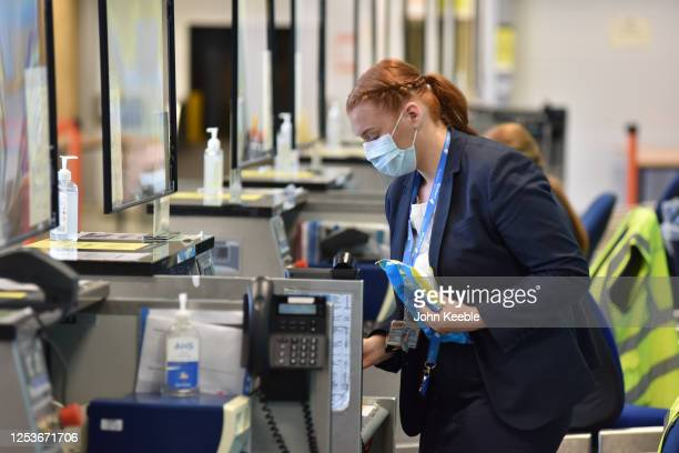 An airport worker cleans while awaiting passengers at the bag drop for Ryanair flight FR2190 to Malaga at London Southend Airport on July 1 2020 in...