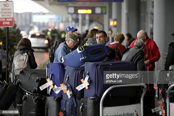 An airport worker organizes luggage on a cart as travelers in the back ground and in the pre checkin line at O'Hare International Airport on December...