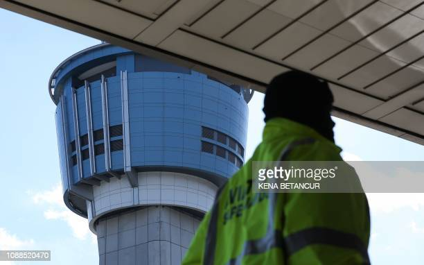 An airport worker passes before the air traffic tower at La Guardia Airport on January 25 2019 in New York The Federal Aviation Administration has...