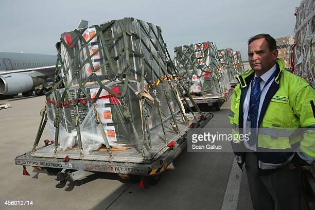 An airport worker stands among pallets of bundled weapons and ammunition from the Bundeswehr, the German armed forces, destined for the Kurdish...