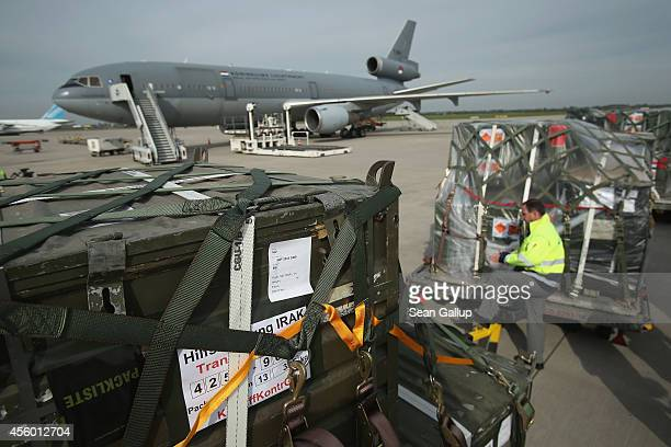An airport worker steps among pallets of bundled weapons and ammunition from the Bundeswehr, the German armed forces, destined for the Kurdish...