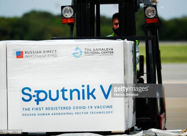 An airport worker uses a forklift to carry a container carrying part of the second batch of 300,000 doses of Sputnik V vaccine from Russia after it's...