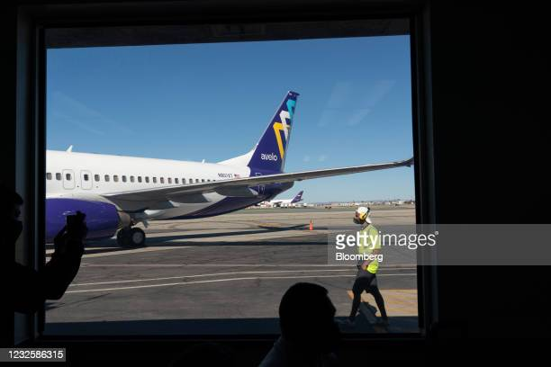An airport worker walks past a Boeing Co. 737-800 aircraft operated by Avelo Airlines ahead of the airline's inaugural flight at Hollywood Burbank...