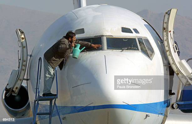 An airport worker washes the windshield of an Ariana Afghan Airlines plane before it makes the first international flight in 5 years from Kabul...