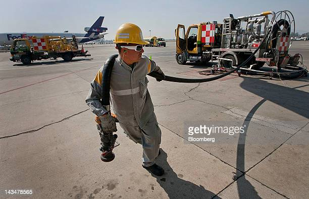 An Airports and Auxiliary Services employee pulls a fuel hose to fill a Volaris airlines plane before departure to Mexico City from Guadalajara...