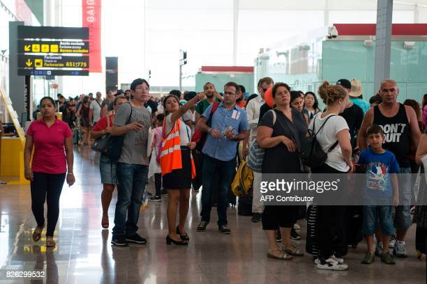 An airport's worker helps a man while other passengers queue to pass the security control at Barcelona's El Prat airport as security agents strike on...