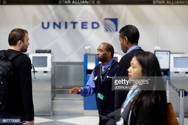 An airpot worker helps a traveler with directions inside the United Airlines terminal at O'Hare International Airport on April 12 2017 in Chicago...